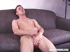 Horny lad jerks off on sofa